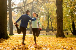 46107878 - young couple stretching legs before jogging in autumn nature